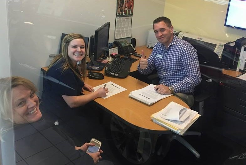 happy customers signing a car loan