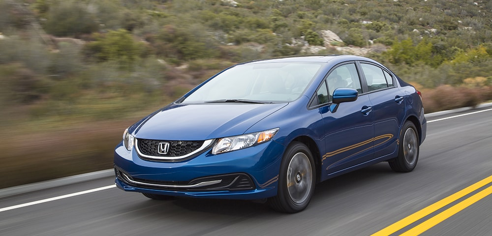 Blue 2015 Honda Civic Sedan driving down the road