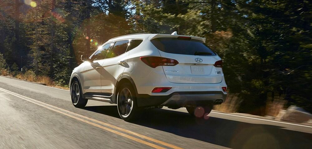 Rear three-quarter view of 2018 Hyundai Santa Fe Sport in a forest.