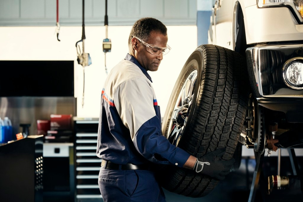 a Ford service technician performs a tire rotation