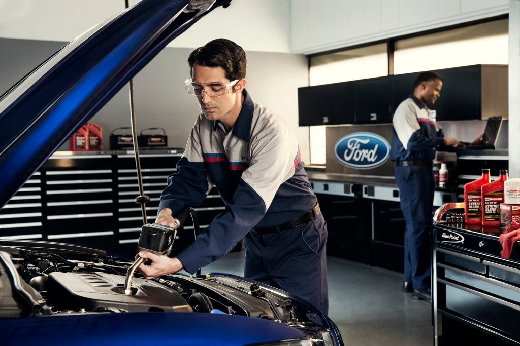 A Ford Service Technician performs an oil change