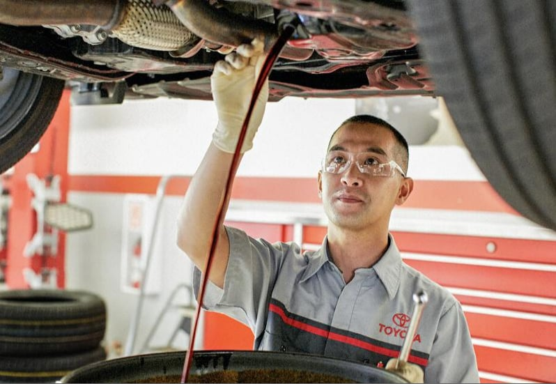 Toyota technician performing an oil change