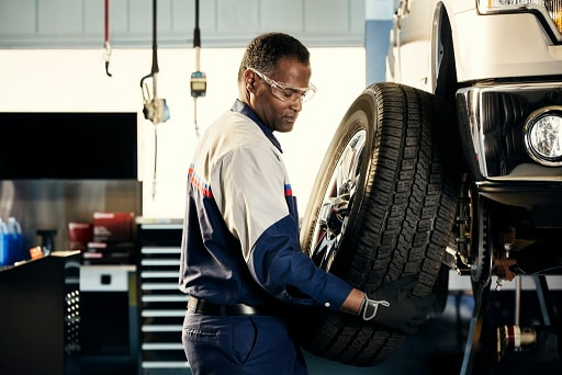 Ford service technician performing tire rotation