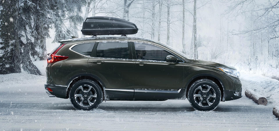 Honda CR-V in winter with storage container on top.