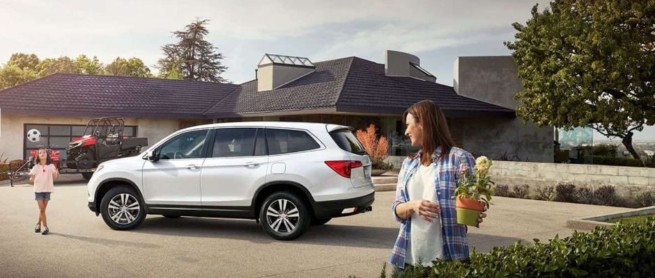 A family at home with their Honda Pilot in the driveway.