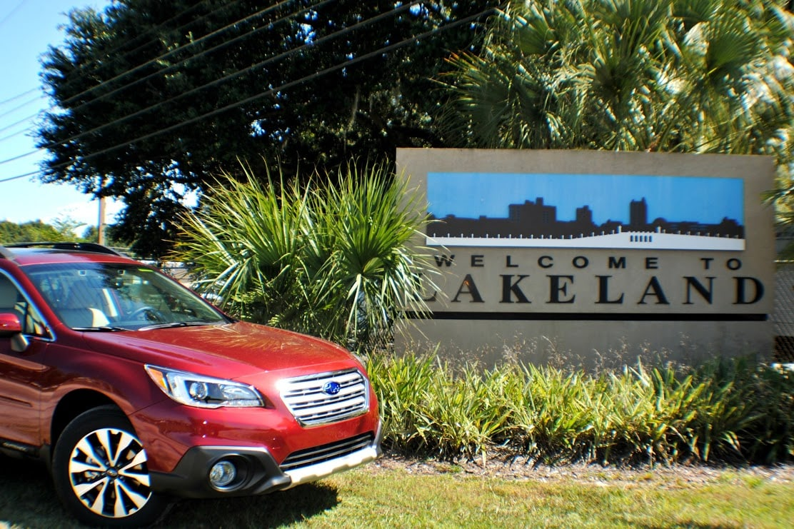 2016 Subaru Outback parked in front of Welcome to Lakeland FL sign