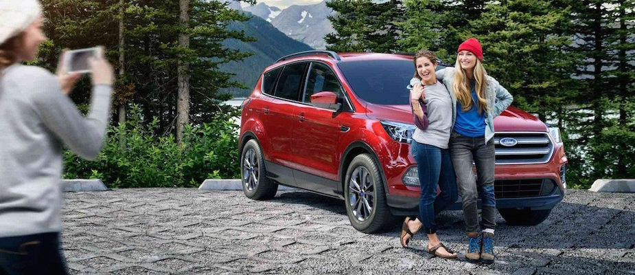 A family taking pictures with their Ford vehicle