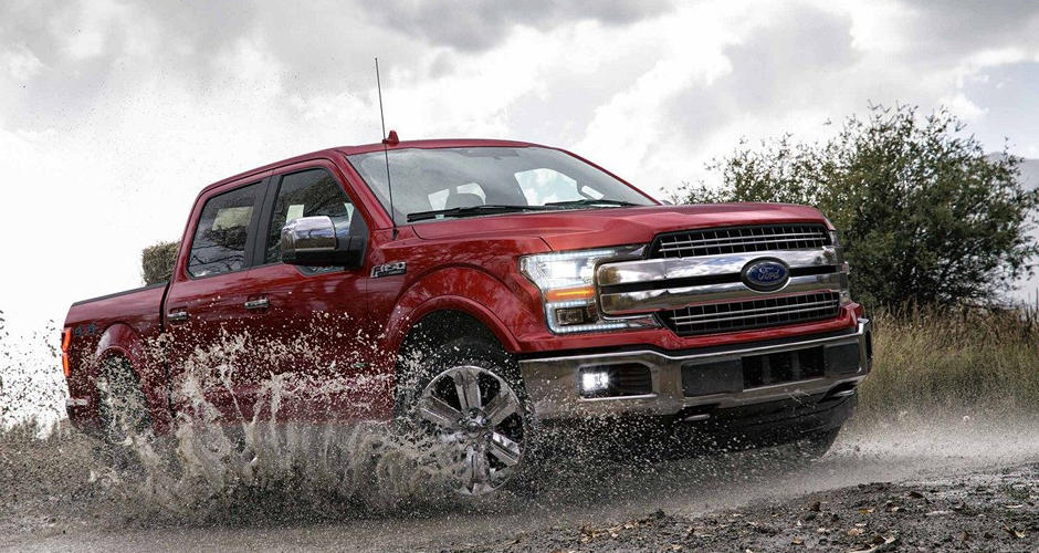 A red 2018 Ford F-150 driving through muddy water