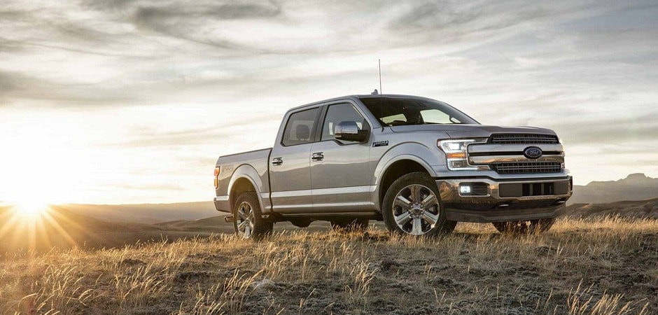 A silver 2018 Ford F-150 parked in the country during a sunset