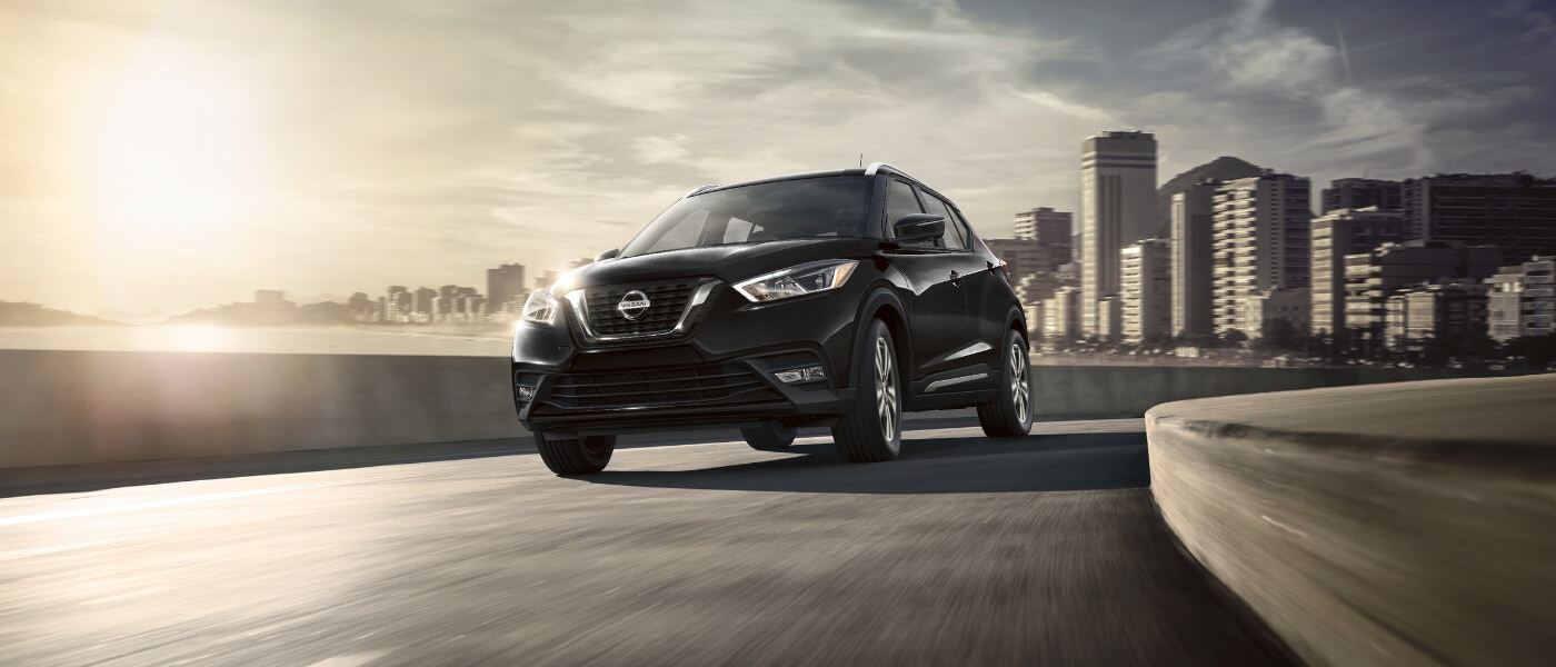 A black 2020 Nissan Kicks driving away through a city on the highway