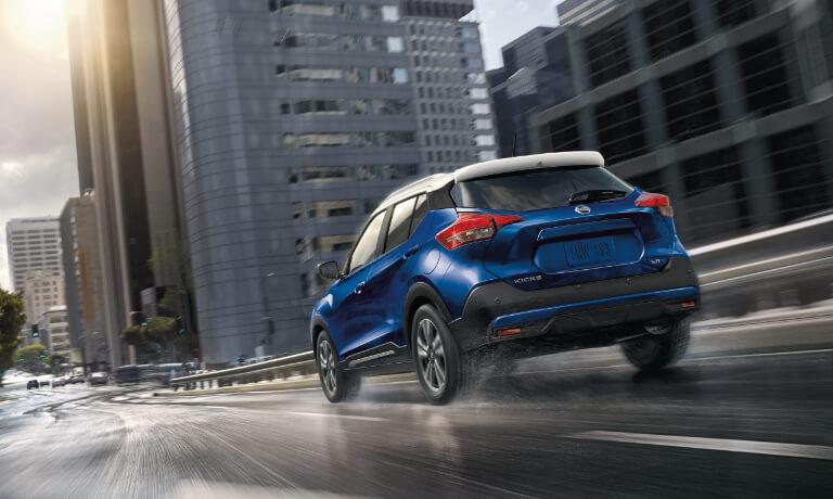 A blue 2020 Nissan Kicks driving through a city street