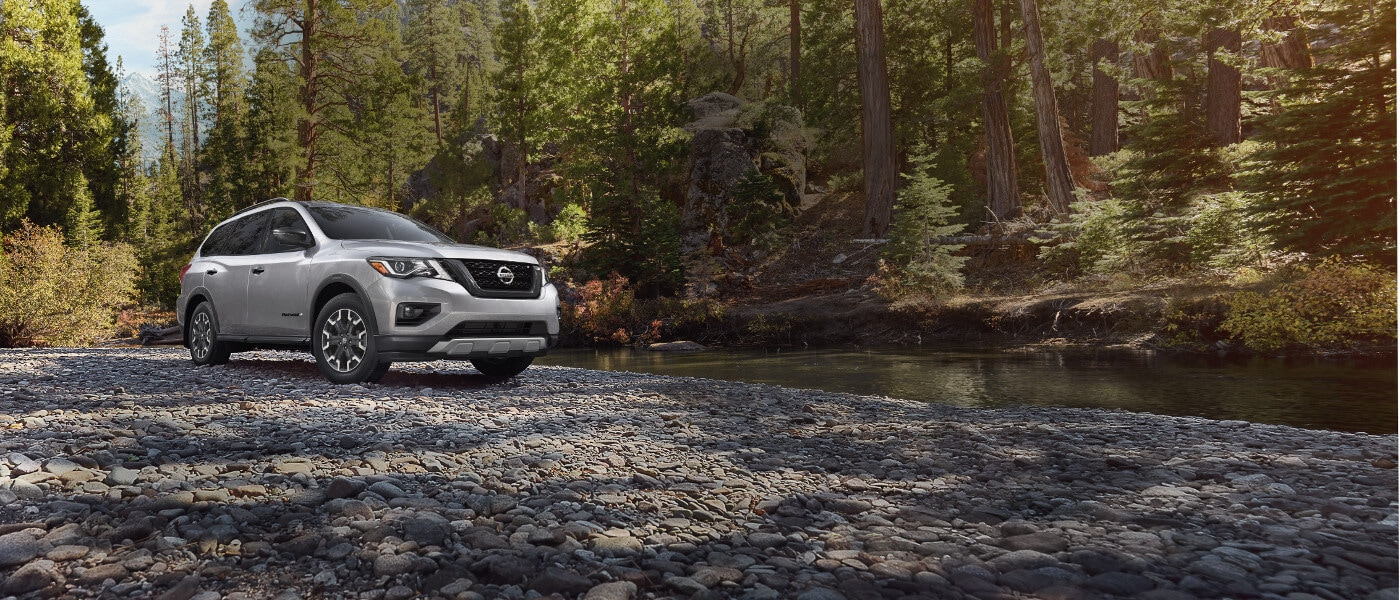 A silver 2020 Nissan Pathfinder parked by a creek in the forest