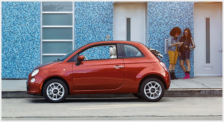 Red 2015 FIAT 500c parked in front of blue building with two females in background