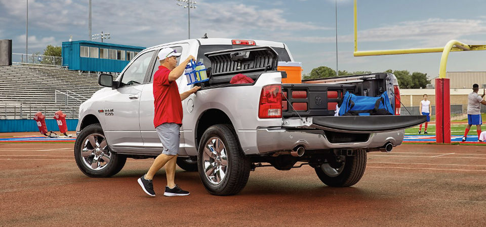 Man loading up sports equipment in the back of a Ram 1500