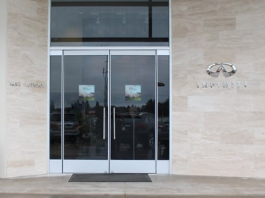 What could be more welcoming than beautiful glass doors, warm stone, and classy Infiniti logo