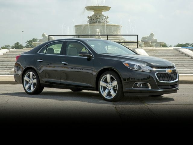 black 2014 Chevrolet Malibu in front of a fountain