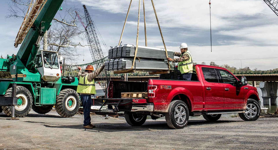 A red 2018 Ford F-150 being loaded up with beams