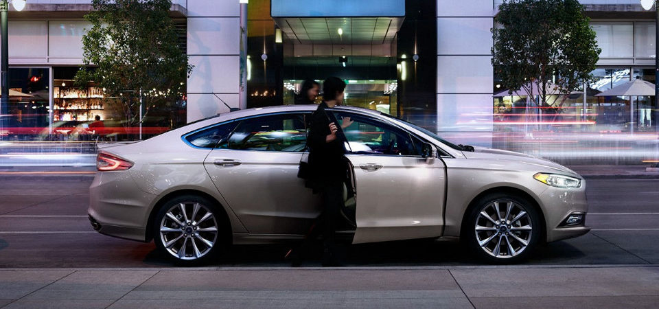 2017 Ford Fusion parked next to a curb with people getting out & Three Fuel Efficient Ford Cars   Springfield IL markmcfarlin.com
