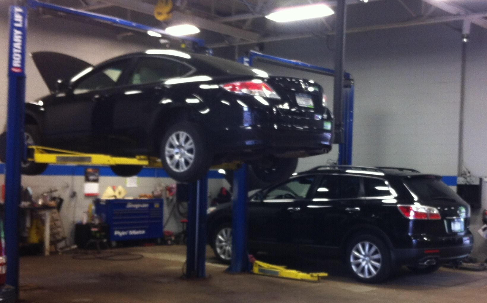 Mazdas on lifts in our Syracuse Repair Shop