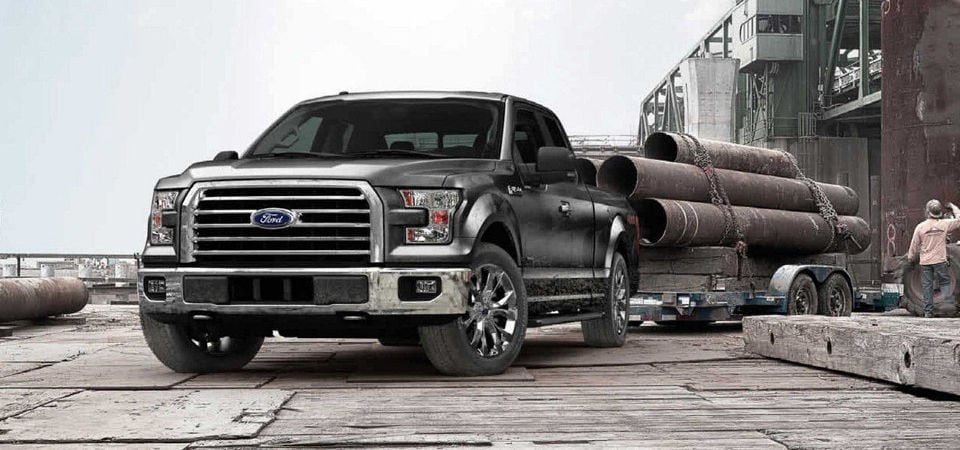Silver Ford F-150 towing a large load of industrial pipes