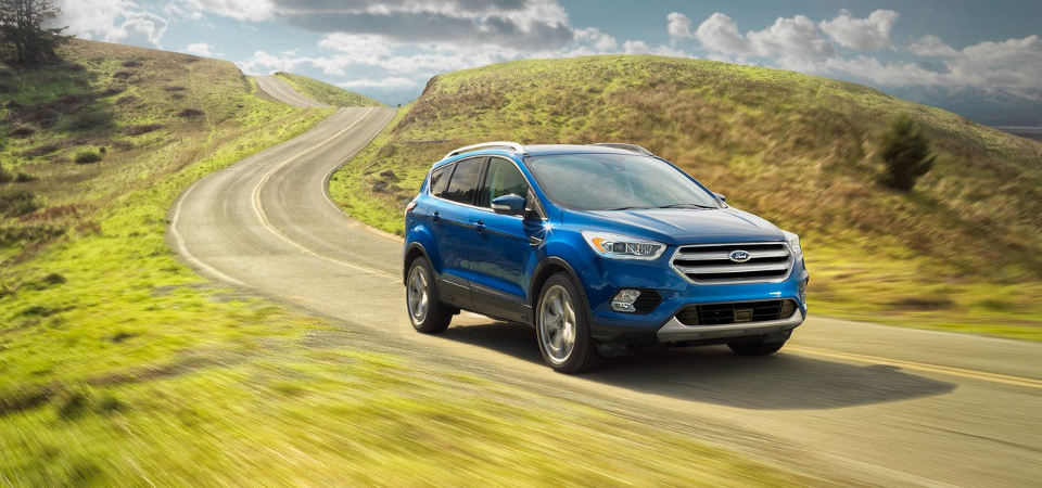 2017 Ford Escape driving along a grassy winding road