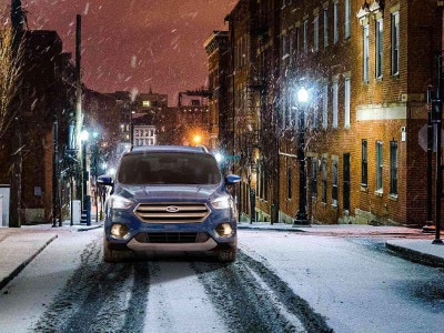 A blue 2018 Ford Escape driving through the snow
