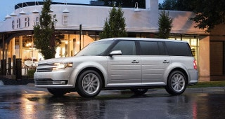 A white Ford Flex Parked outside of a restaurant