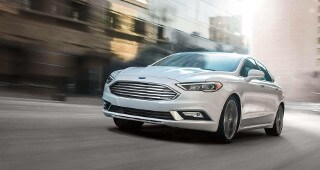 A white Ford Fusion driving through the city