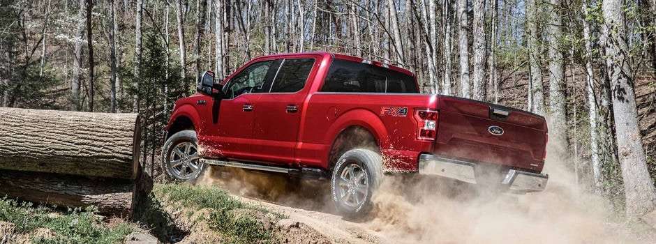 a red 2018 Ford F-150 driving up a dirt road