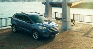 A blue Ford Escape parked by the water