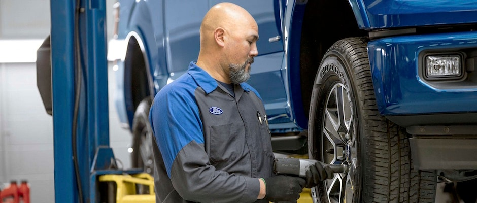 A Ford technician working on a set of tires