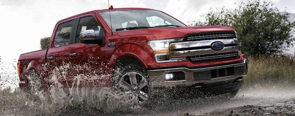 A red 2018 Ford F-150 driving through the mud