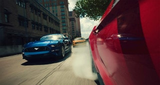 Ford Mustangs driving through the city streets