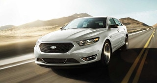 A silver Ford Taurus driving down the country road