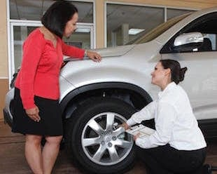 A technician showing a woman what's wrong with her tires