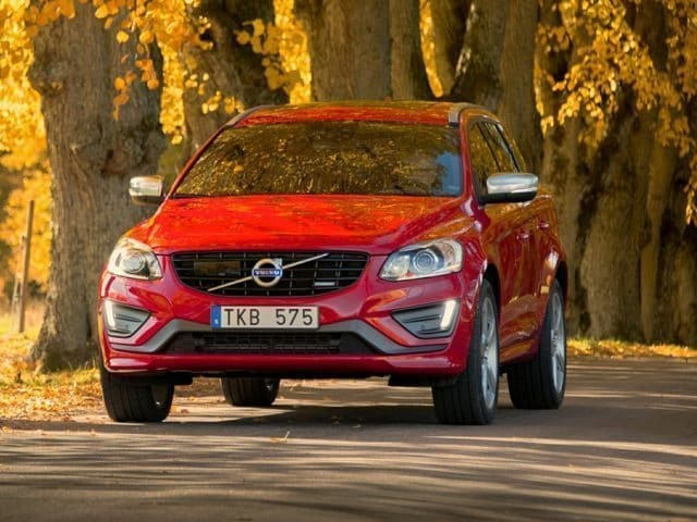 Image of a 2015 Volvo xc60 driving on a tree-lined lane in fall