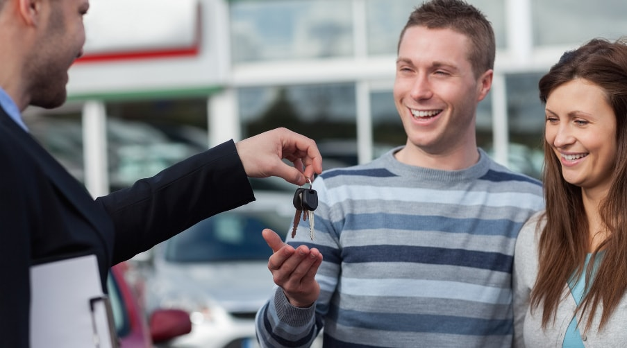 Couple getting keys to new car