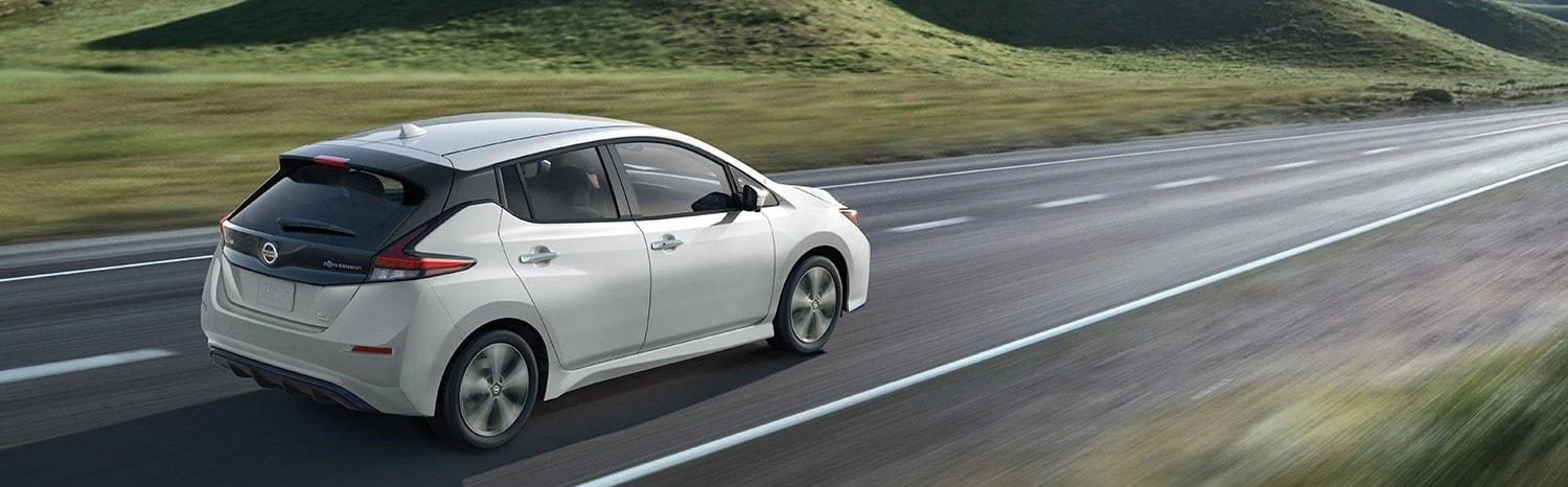 2021 Nissan Leaf driving down a road with green hills in the background