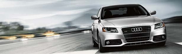 A new silver Audi sedan speeding down a runway