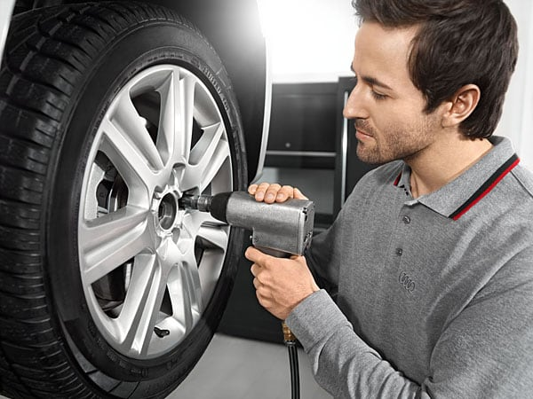 Audi service technician working on tire