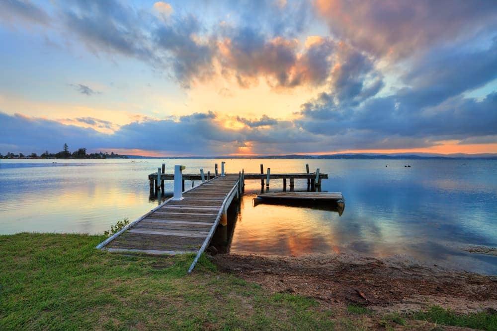 lake and board walk amongst sunset