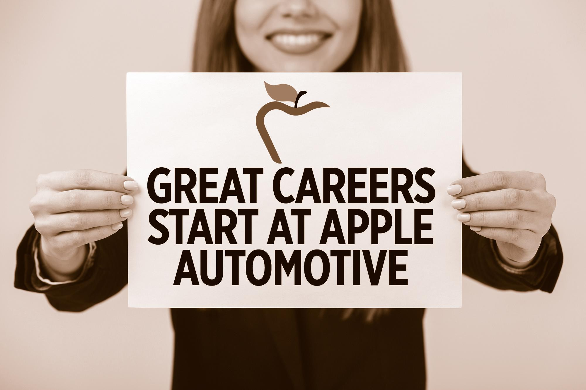 smiling woman, holding a sign that says great careers start at Apple Automotive