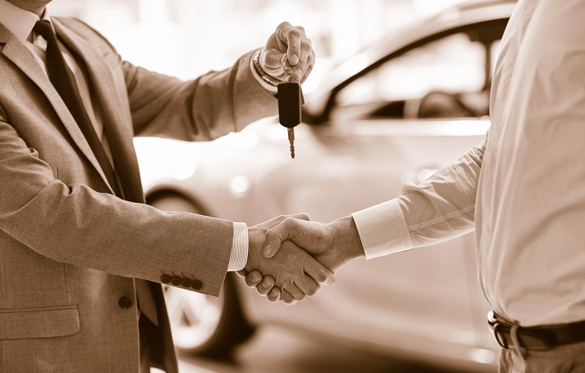 two men shaking hands; one handing over keys to new vehicle