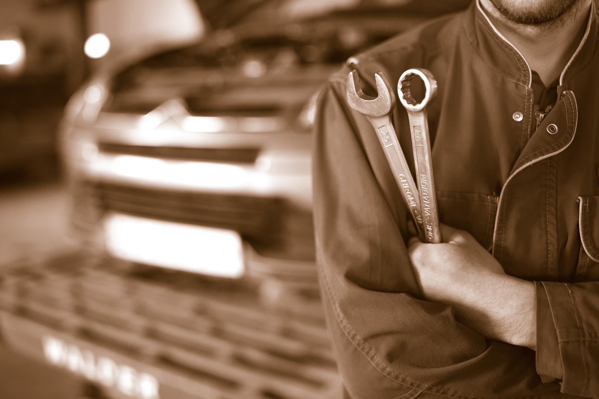 auto mechanic holding wrenches