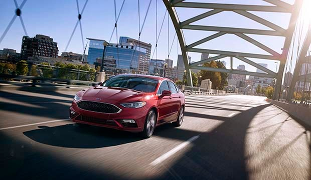 car driving across bridge; red 2018 Ford Fusion