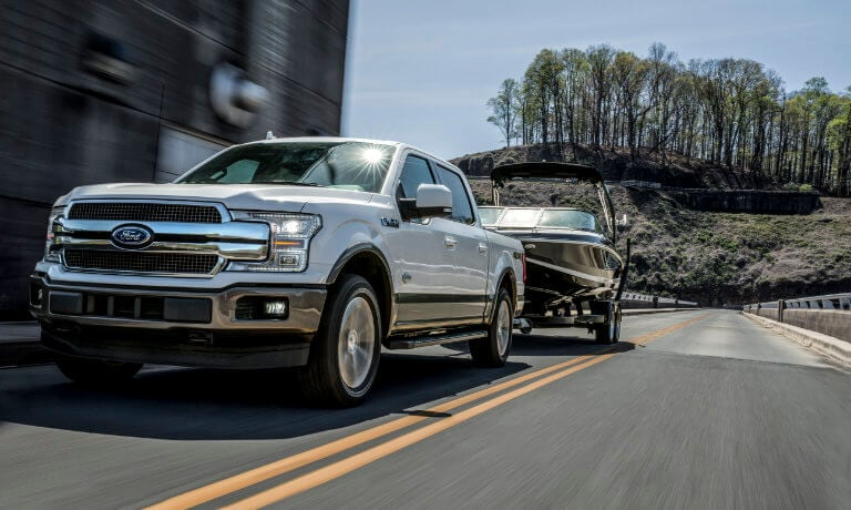 2019 Ford F-150 towing boat down street