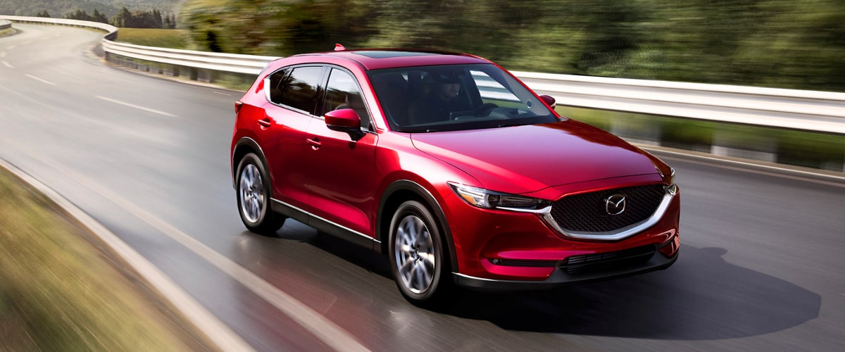 Red 2019 Mazda CX-5 driving exterior view