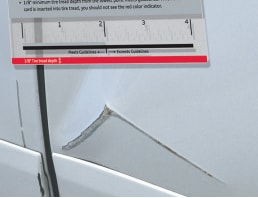 Audi Wear and Use Guide being used to measure a large scratch
