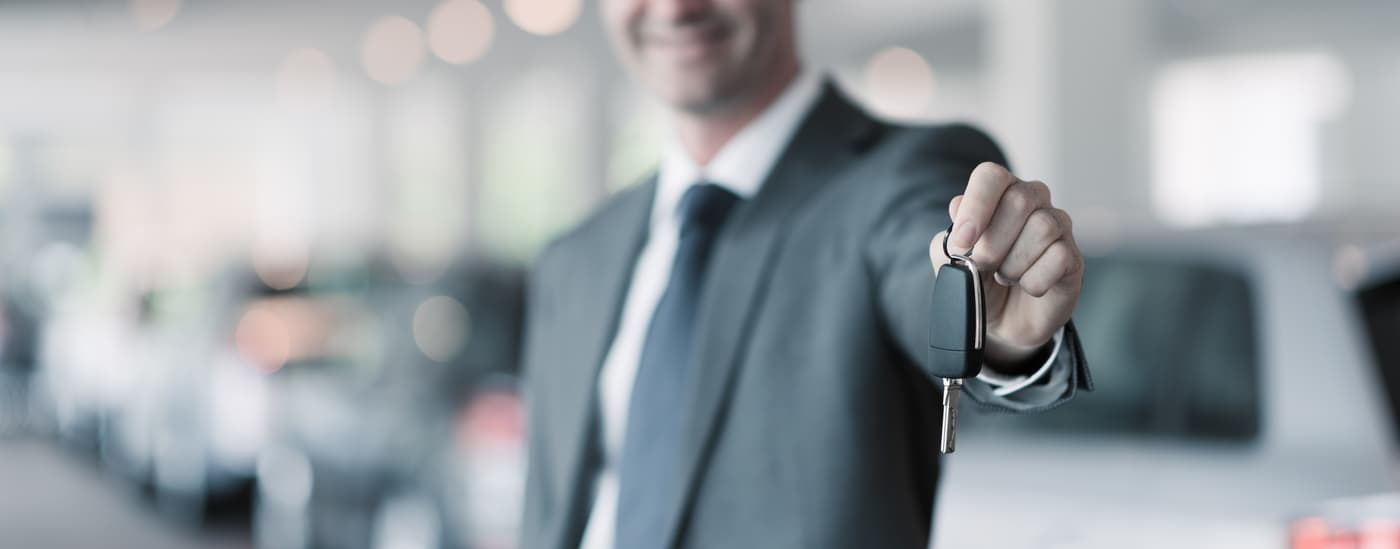Luxury auto salesman handing over keys to car
