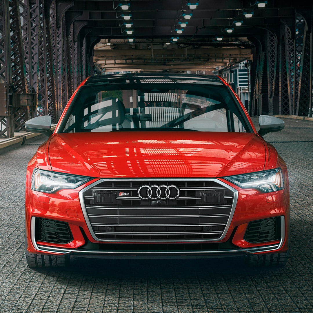 Audi Owings Mills is a Car Dealership in Reisterstown near Owings Mills MD | Red MY20 Audi S6 driving on city bridge
